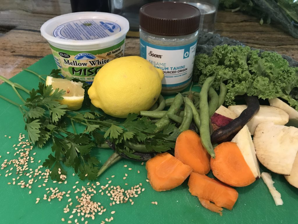 Cutting board with cut up veggies and ingredients for miso-tahini sauce