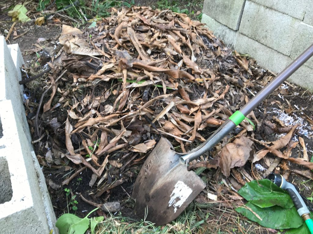 compost pile on the ground with shovel